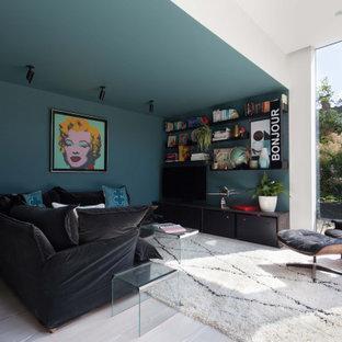 ロンドンの広いモダンスタイルのおしゃれなオープンリビング (ゲームルーム、青い壁、淡色無垢フローリング、暖炉なし、据え置き型テレビ、白い床) の写真