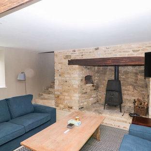 Idées déco pour une salle de séjour campagne de taille moyenne et ouverte avec salle de jeu, un mur beige, un sol en calcaire, un poêle à bois, un manteau de cheminée en pierre, un téléviseur fixé au mur et un sol beige.