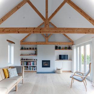 Immagine di un soggiorno scandinavo di medie dimensioni e chiuso con pavimento beige, pareti bianche, cornice del camino in mattoni, TV autoportante, pavimento in legno verniciato e camino classico