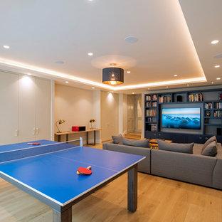 Foto de sala de juegos en casa abierta, contemporánea, grande, con paredes blancas, suelo de madera clara, televisor colgado en la pared y suelo beige