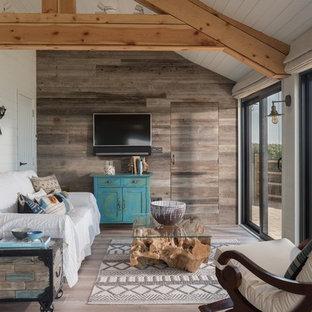 Diseño de sala de estar cerrada, costera, de tamaño medio, con paredes blancas, televisor colgado en la pared y suelo gris