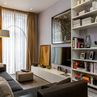 This is an example of a contemporary enclosed family and games room in London with purple walls, light hardwood flooring and a wall mounted tv.