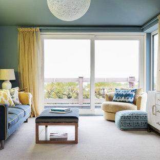 サセックスのビーチスタイルのおしゃれなファミリールーム (青い壁、カーペット敷き、壁掛け型テレビ、白い床) の写真