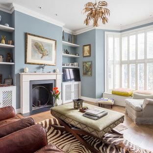 Idéer för att renovera ett mellanstort eklektiskt allrum, med blå väggar, mellanmörkt trägolv, en standard öppen spis, en spiselkrans i metall och brunt golv