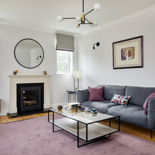 This is an example of a medium sized traditional family and games room in London with purple walls, a wood burning stove, a freestanding tv and light hardwood flooring.