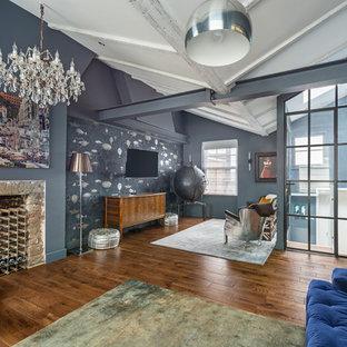 ロンドンのインダストリアルスタイルのおしゃれなオープンリビング (青い壁、淡色無垢フローリング、標準型暖炉、石材の暖炉まわり、壁掛け型テレビ、茶色い床) の写真
