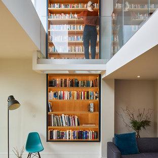 Modelo de sala de estar con biblioteca abierta, contemporánea, con paredes blancas y suelo de madera clara