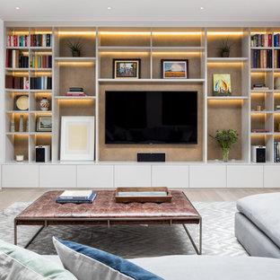 Diseño de sala de estar con biblioteca actual, extra grande, sin chimenea, con paredes blancas, suelo de madera clara, pared multimedia y suelo beige