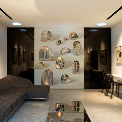 Example of a mid-sized trendy enclosed concrete floor and gray floor family room design in London with white walls and a wall-mounted tv
