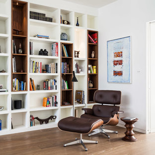 Design ideas for a contemporary family and games room in London with a reading nook, white walls and medium hardwood flooring.