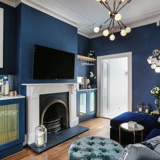 Cette photo montre une salle de séjour éclectique fermée avec un bar de salon, un mur bleu, un sol en bois brun, une cheminée standard et un téléviseur fixé au mur.