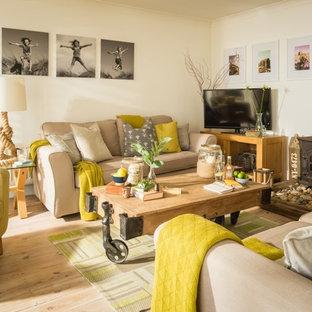 サセックスの中サイズのビーチスタイルのおしゃれなファミリールーム (白い壁、淡色無垢フローリング、薪ストーブ、据え置き型テレビ、ベージュの床、金属の暖炉まわり) の写真