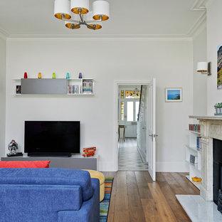 Ispirazione per un soggiorno contemporaneo di medie dimensioni e aperto con pareti bianche, pavimento in legno massello medio, camino classico e cornice del camino in pietra