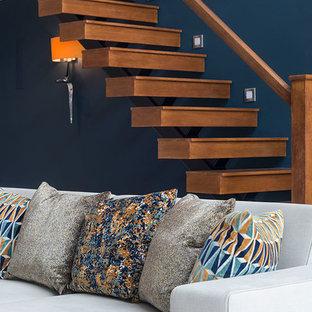 サリーの大きいコンテンポラリースタイルのおしゃれなファミリールーム (ゲームルーム、青い壁、ラミネートの床、壁掛け型テレビ、グレーの床) の写真