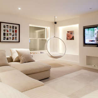 Contemporary enclosed family and games room in London with beige walls, carpet, a wall mounted tv and beige floors.
