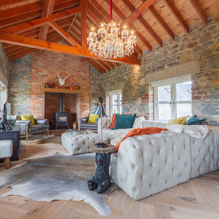 Inspiration for a farmhouse games room in Belfast with multi-coloured walls, light hardwood flooring, a wood burning stove and a freestanding tv.