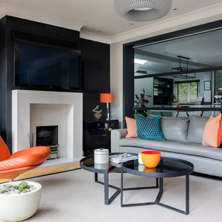 Medium sized contemporary games room in London with a plastered fireplace surround, grey walls, light hardwood flooring, a standard fireplace and a wall mounted tv.