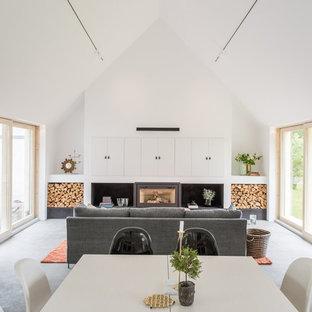 Offenes, Großes, Fernseherloses Skandinavisches Wohnzimmer mit weißer Wandfarbe, Betonboden, Gaskamin und Kaminumrandung aus Metall in Stockholm