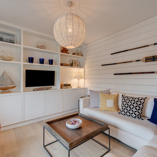Example of a coastal open concept light wood floor family room design in Devon with white walls, no fireplace and a media wall