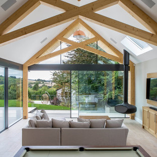 This is an example of a contemporary family room in Buckinghamshire with a hanging fireplace.