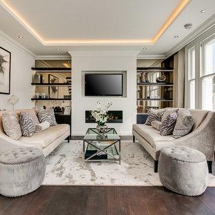 Diseño de sala de estar abierta, clásica renovada, de tamaño medio, con paredes grises, suelo de madera oscura, chimenea lineal, marco de chimenea de metal, televisor colgado en la pared y suelo marrón