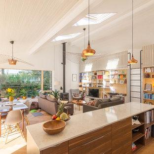 Ejemplo de sala de estar abierta, nórdica, grande, con suelo de madera clara, suelo beige, paredes blancas, estufa de leña y pared multimedia