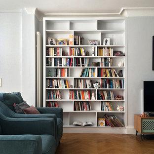ロンドンの中サイズのコンテンポラリースタイルのおしゃれな独立型ファミリールーム (ミュージックルーム、青い壁、無垢フローリング、標準型暖炉、漆喰の暖炉まわり、据え置き型テレビ、茶色い床) の写真