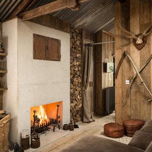 Imagen de sala de estar con biblioteca rústica con suelo de madera clara, chimenea tradicional, televisor retractable y marco de chimenea de hormigón