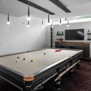 Medium sized contemporary enclosed games room in Gloucestershire with a game room, white walls, carpet, a wall mounted tv and brown floors.