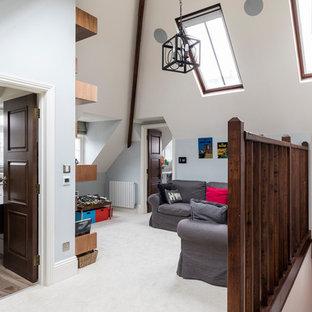 ロンドンの中サイズのコンテンポラリースタイルのおしゃれなファミリールーム (ゲームルーム、青い壁、カーペット敷き、埋込式メディアウォール、ベージュの床) の写真
