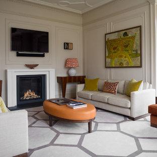 Modelo de sala de estar clásica renovada con paredes beige, chimenea tradicional, televisor colgado en la pared y suelo multicolor