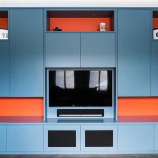 ロンドンの大きいモダンスタイルのおしゃれな独立型ファミリールーム (ゲームルーム、青い壁、濃色無垢フローリング、暖炉なし、金属の暖炉まわり、埋込式メディアウォール、茶色い床) の写真