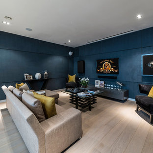 Photo of a medium sized classic enclosed games room in Other with blue walls, a wall mounted tv, beige floors and light hardwood flooring.