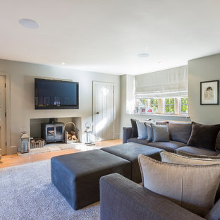 Mid-sized cottage enclosed medium tone wood floor and beige floor family room photo in Gloucestershire with gray walls, a wall-mounted tv and a wood stove