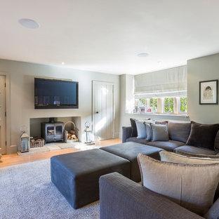 Idée de décoration pour une salle de séjour champêtre fermée et de taille moyenne avec un mur gris, un téléviseur fixé au mur, un poêle à bois, un sol en bois brun et un sol beige.