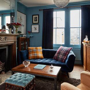 ロンドンのエクレクティックスタイルのおしゃれな独立型ファミリールーム (ホームバー、青い壁、無垢フローリング、標準型暖炉、金属の暖炉まわり、茶色い床) の写真