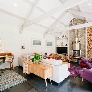 コーンウォールの中サイズのビーチスタイルのおしゃれなファミリールーム (白い壁、薪ストーブ、グレーの床、埋込式メディアウォール) の写真