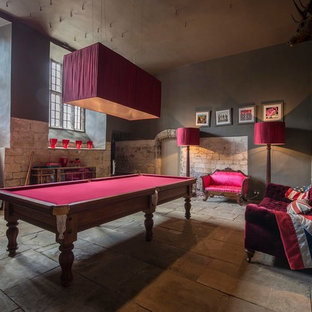 Inspiration for a medium sized eclectic games room in Other with grey walls, a game room, a standard fireplace and a stone fireplace surround.