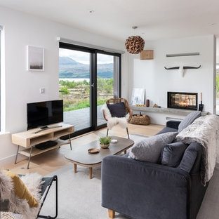 Design ideas for a medium sized scandi games room in Cornwall with white walls, light hardwood flooring, a two-sided fireplace, a freestanding tv and beige floors.