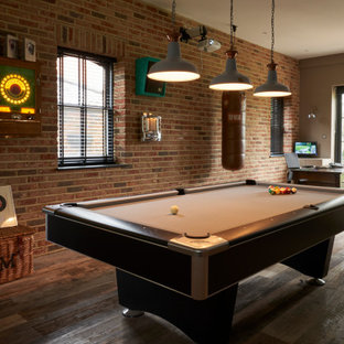 Photo of a bohemian games room in London with a game room, brown walls, dark hardwood flooring, brown floors and brick walls.