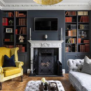 エセックスの広いトランジショナルスタイルのおしゃれな独立型ファミリールーム (青い壁、無垢フローリング、標準型暖炉、石材の暖炉まわり、壁掛け型テレビ、茶色い床、板張り壁) の写真