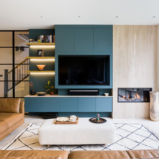 Inspiration for a scandinavian open plan family and games room in London with blue walls, a ribbon fireplace and a built-in media unit.