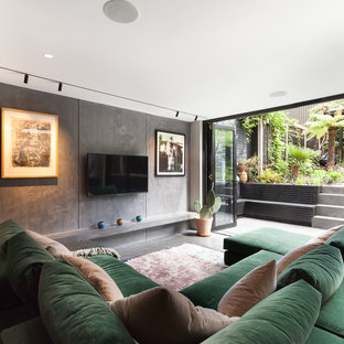 Inspiration for a medium sized contemporary open plan family and games room in London with grey walls, concrete flooring, a wall mounted tv and grey floors.