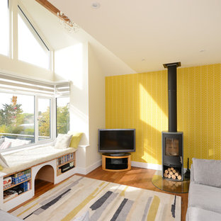 Photo of an eclectic games room in Kent with yellow walls, medium hardwood flooring, a wood burning stove, a metal fireplace surround, a freestanding tv and brown floors.