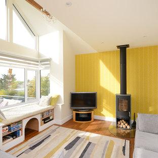 Imagen de sala de estar ecléctica con paredes amarillas, suelo de madera en tonos medios, estufa de leña, marco de chimenea de metal, televisor independiente y suelo marrón