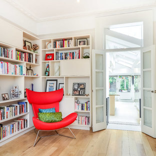 Contemporary enclosed games room in Sussex with a reading nook, white walls, light hardwood flooring and beige floors.
