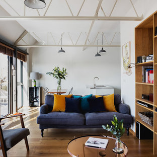 Design ideas for a medium sized contemporary open plan family and games room in London with white walls, medium hardwood flooring, a reading nook and no fireplace.