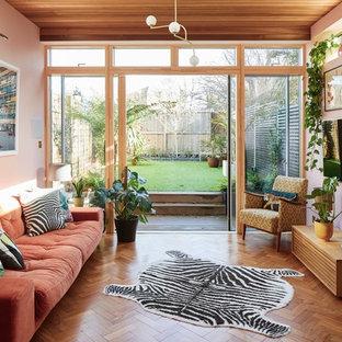 Foto de sala de estar vintage con paredes rosas, suelo de madera en tonos medios, marco de chimenea de ladrillo y televisor colgado en la pared