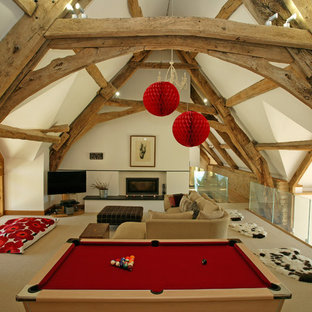 This is an example of a large country mezzanine family and games room in Dorset with white walls, carpet, a standard fireplace, a corner tv, a game room and beige floors.