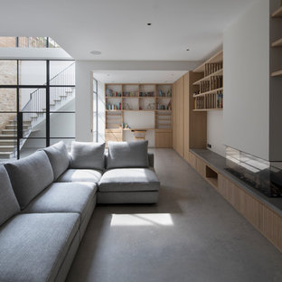 Inspiration for an expansive modern open plan family and games room in London with white walls, a ribbon fireplace, a plastered fireplace surround, concrete flooring and grey floors.